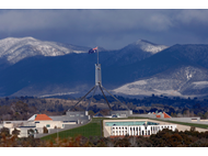 View of Parliament House with light snow on the Brindabellas
