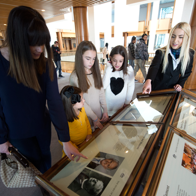 Tour guide showing young family information displays at Parliament House