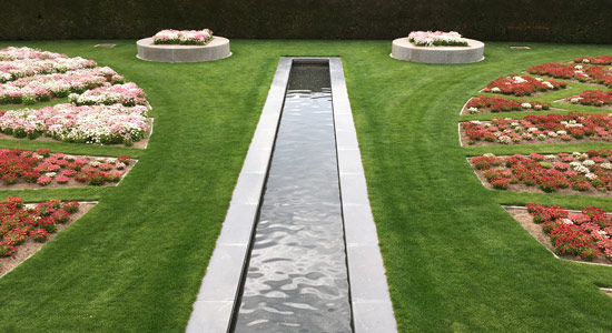 A water feature runs through the lawns of the Formal Gardens which is surrounded by flower beds.