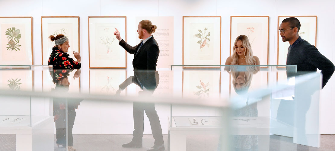 A guide with visitors exploring the exhibition The Voyage of Discovery: Sir Joseph Banks' Florilegium.