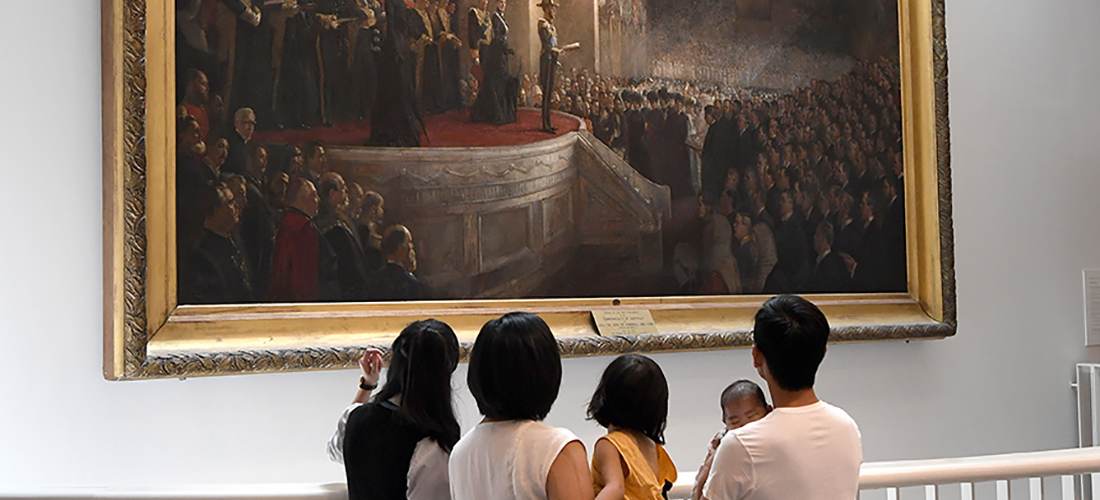 A guide discusses a painting by Tom Roberts 'Opening of the First Parliament of the Commonwealth of Australia by H.R.H The Duke of Cornwall and York (Later King George V), May 9, 1901'