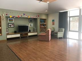 Figure 1.9 & 1.10 (from left to right): photo of indoor communal area; and view of outdoor communal area, including fire pit where family members can come and visit residents and participate in ceremonial activities.