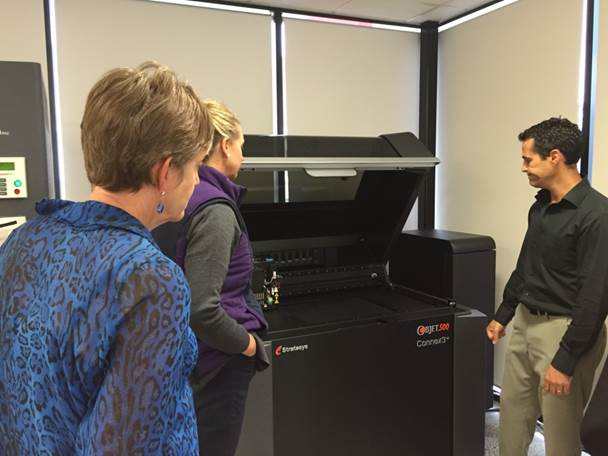 Figure 6.1: Committee members inspect a 3D printer