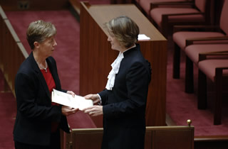 A message from the House of Representatives is delivered by the Serjeant-at-Arms and collected by a clerk at the table at the bar of the Senate (Photo courtesy of AUSPIC)