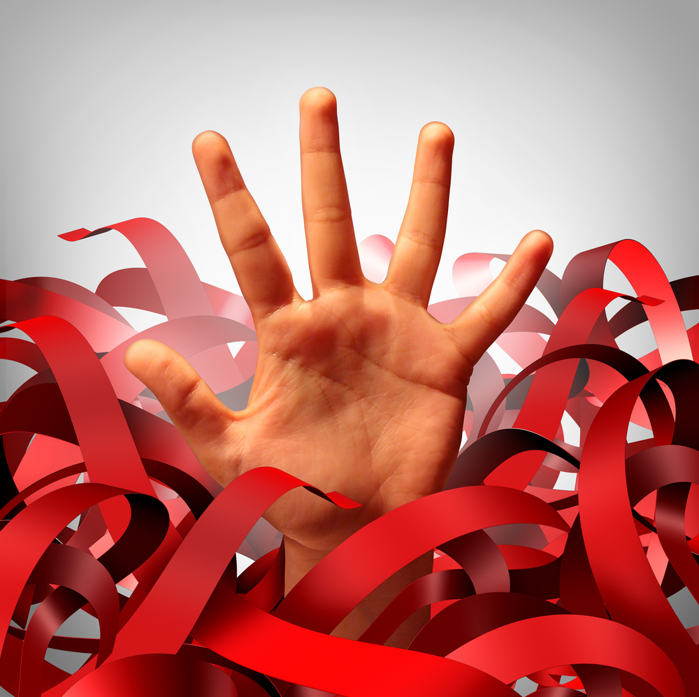 Bureaucratic red tape problem as a human hand tangled in bureaucracy and regulations as a business concept and symbol of government gridlock or corporate regulatory confusion.