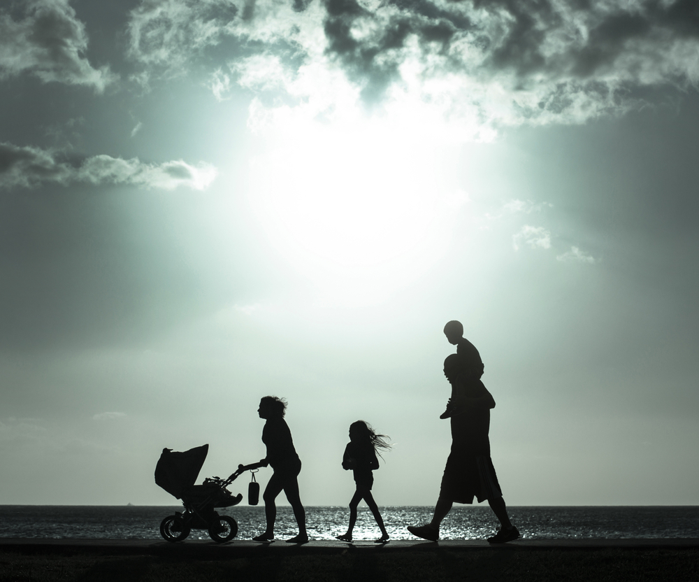 Silhouette of mother pushing baby cart with family