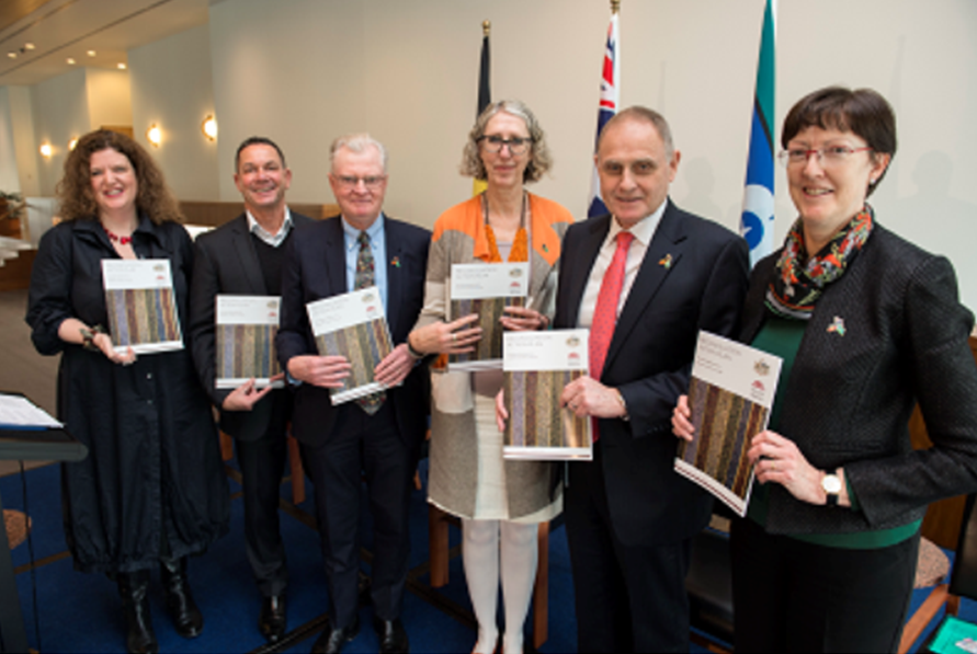 Image of Australian parliamentary service staff holding copies of the Reconciliation Action Plan