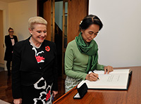 Aung San Suu Kyi signs the Visitors' book in the Speaker's Suite