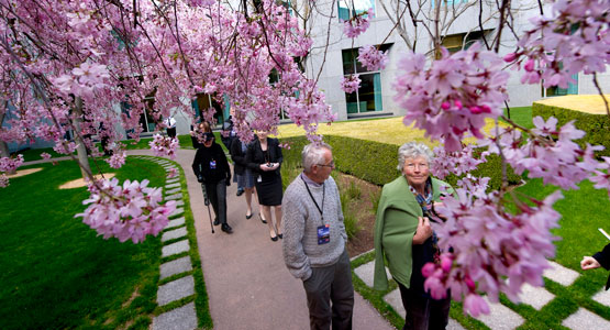 A gardener speaks with visitors in the courtyards of Australian Parliament House.