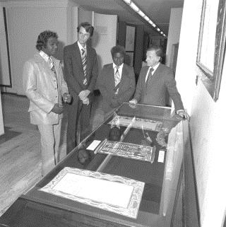 Yolngu leaders Gallarwuy Yunupingu (left) and Silas Roberts at Parliament House in 1977 with Jeremy Long and the Minister for Aboriginal Affairs, THE Hon. Ian Viner (right), looking at the two bark petitions presented to the House of Representatives in 1963.