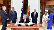 Sri Lankan Prime Minister Ranil Wickremesinghe signs the visitors' book at Parliament House